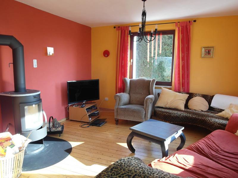 Orange-rotes Wohnzimmer mit Leopardenmuster-Couch und einem Ofen
