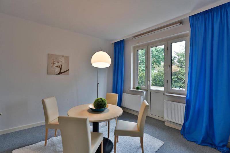 Ein simpel eingerichtetes Zimmer mit einem Tisch in der Mitte und einer Fenstertür