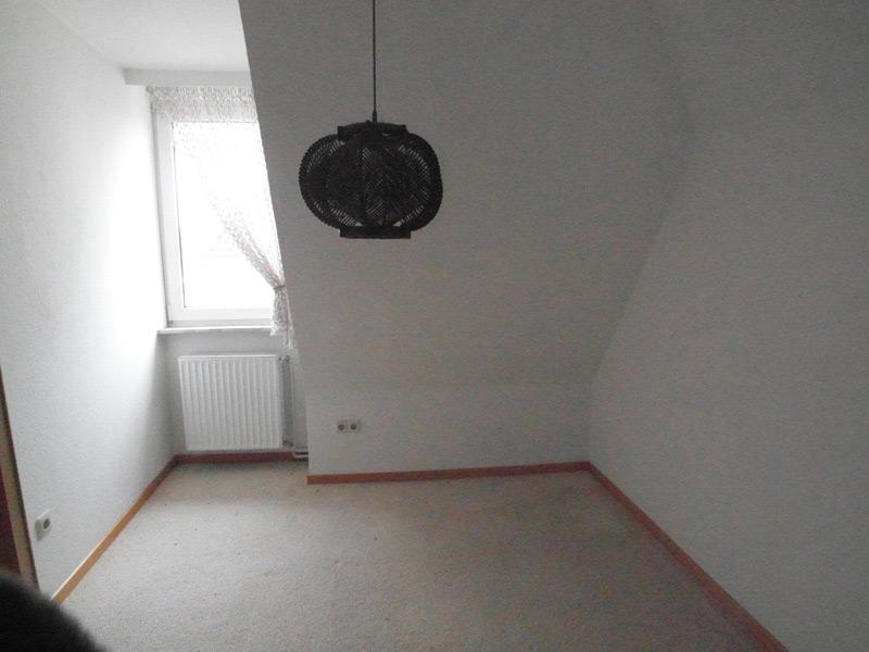 Leeres, weißes Zimmer mit einer Dachschräge und einem Lampignon-Lampenschirm