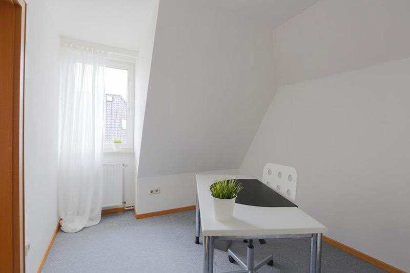 Weißes Arbeitszimmer mit einem kleinen Tisch und einem Fenster nebst einer Dachschräge