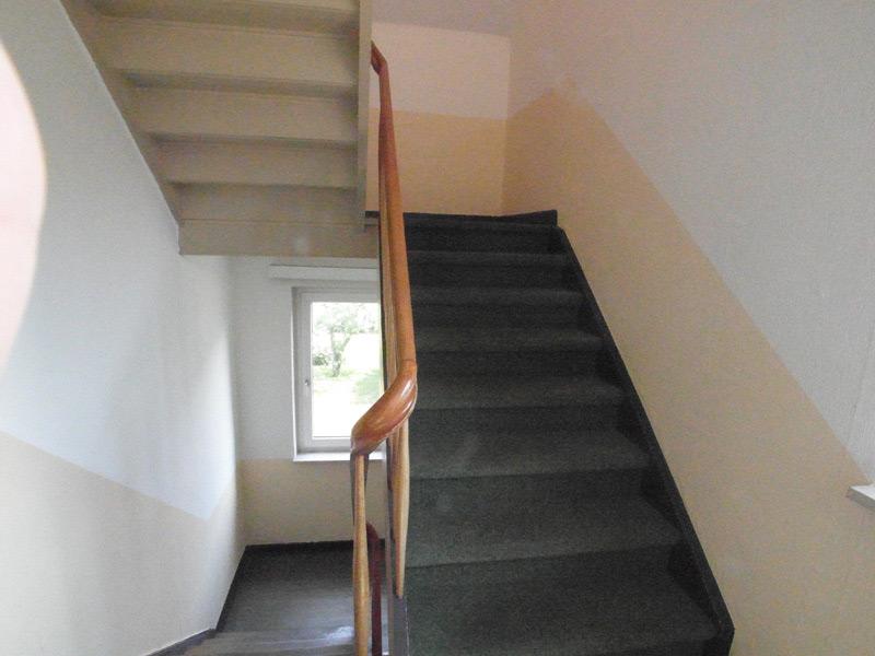 Ein Treppenhaus mit einem beigen Farbstreifen, der dem Lauf der Treppe folgt