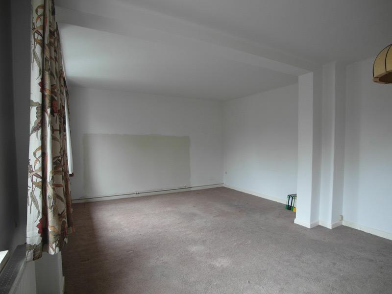 Weißes, leeres Zimmer mit einem grauen Teppichboden