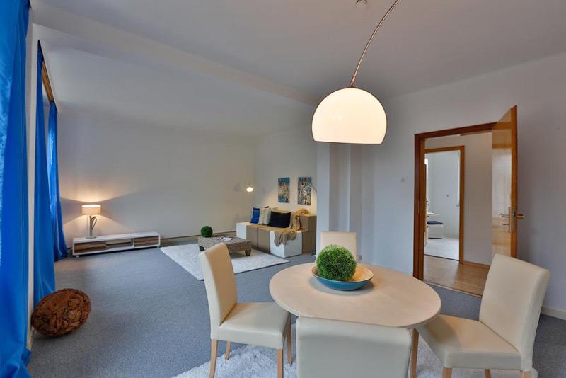 Weißes Wohnzimmer mit grauem Boden und blauen Vorhängen