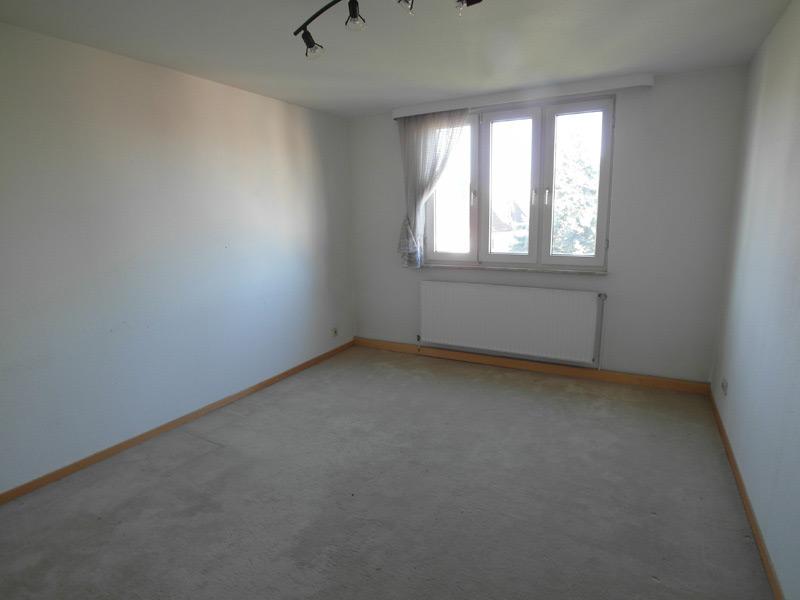 Leeres Zimmer mit Fensterreihe aus drei schmalen Fenstern