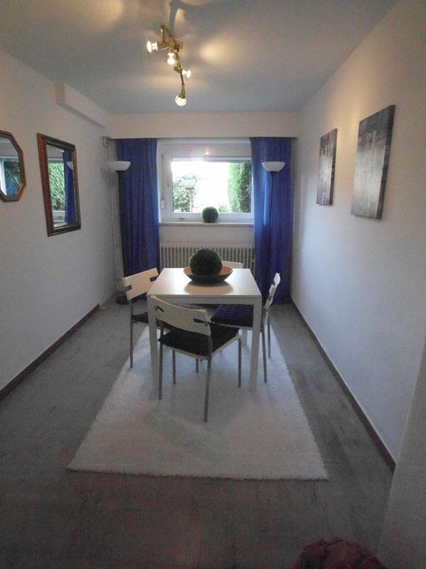 Weißes Esszimmer mit grauem Boden und weißem Esstisch auf einem Teppich