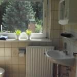 Beiges Bad mit einem braunen Mosaikfliesen Boden und kleinen Zierpflanzen auf dem Fensterbrett