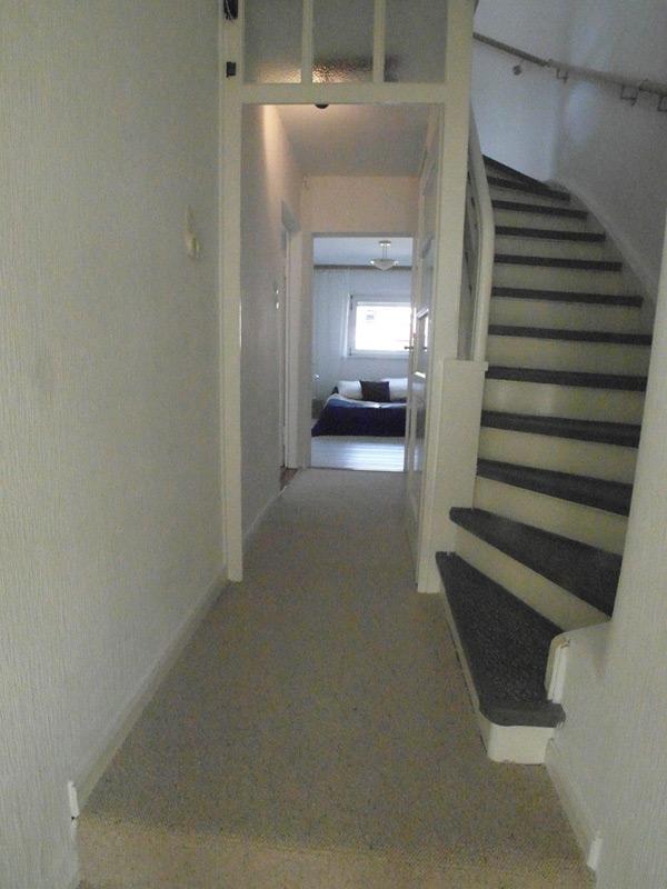 Weißes Treppenhaus mit einem Flur der parallel zur Treppe verläuft