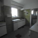 Weiße Küche mit grünen Wandfliesen und einer weißen Küchenzeile