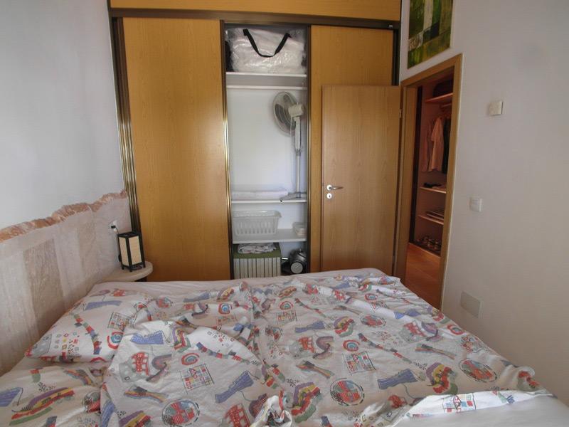Bett mit einer bunten Decke vor einem Holz-Wandschrank