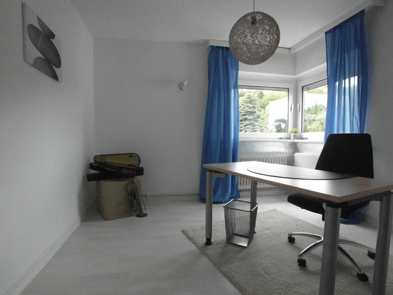 Weißes Arbeitszimmer mit einem hellgrauen Boden und royalblauen Vorhängen