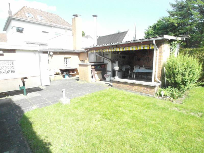 Überdachte Annex-Terrasse in einem grünen Garten bei Sonnenschein