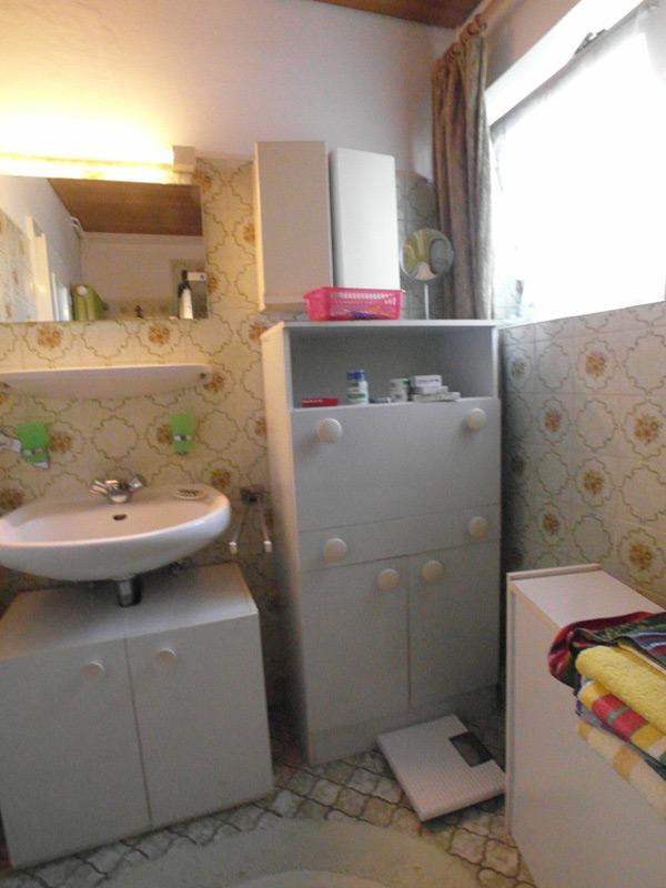Bad mit alten, floralen Fliesen und weißem Mobiliar