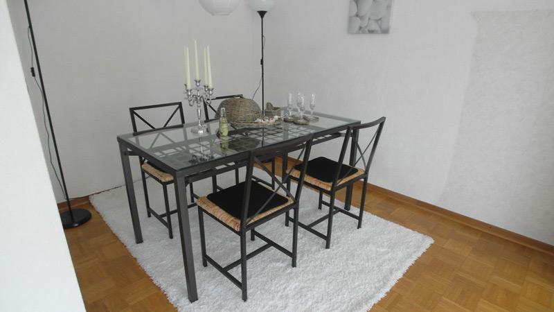 Glastisch mit Metallrahmen und zugehörigen Stühlen auf einem weißen Teppich