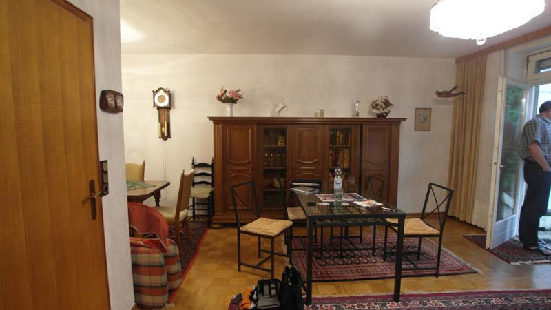 Weißes Wohnzimmer mit einem alten Holzschrank und drei Orientteppichen