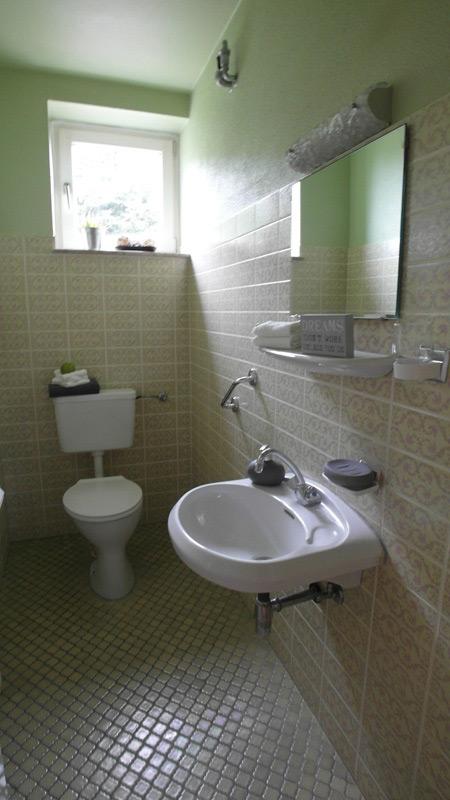 Altmodisches Badezimmer mit floralen Wandfliesen und einem Boden aus Mosaikfliesen