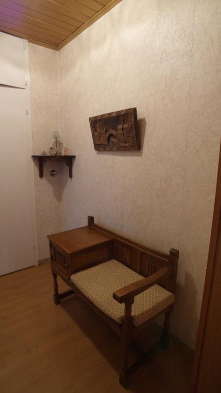 Eine Holz-Sitzbank unter dem Holzschnitt einer Stadt