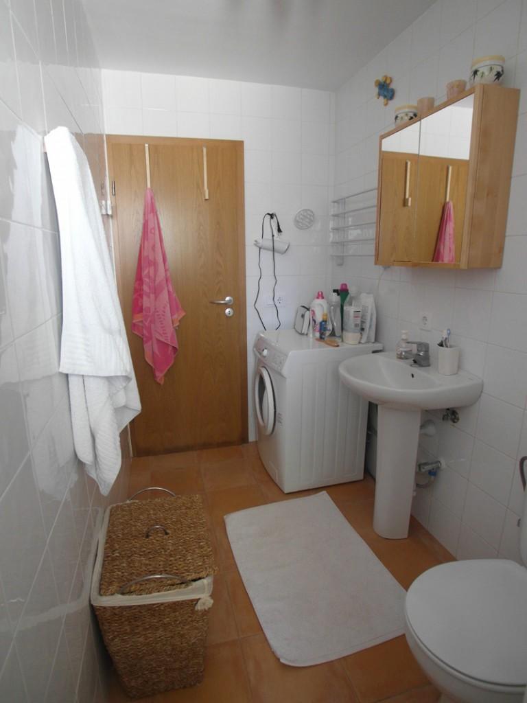 Weißes Badezimmer mit braunen Bodenfliesen