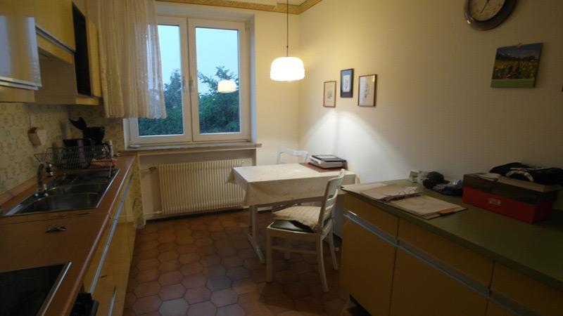 Weiße Küche mit braunen Fliesen und einer senfgelben Küchenzeile