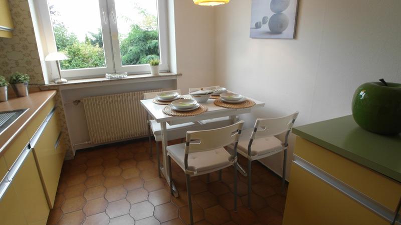 Weiße Küche mit braunen Bodenfliesen und einem Küchentisch für vier Personen