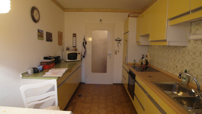 Weiße Küche mit braunem Boden und einer senfgelben Küchenzeile