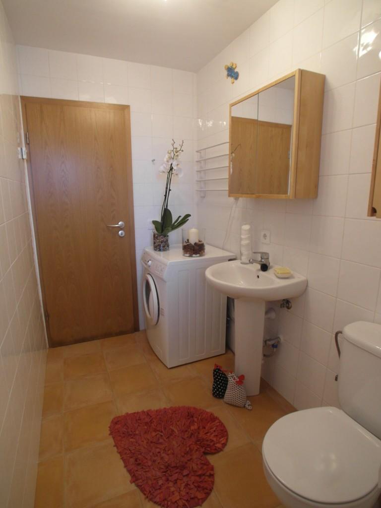 Weißes Badezimmer mit braunen Bodenfliesen und einem herzförmigen Teppich