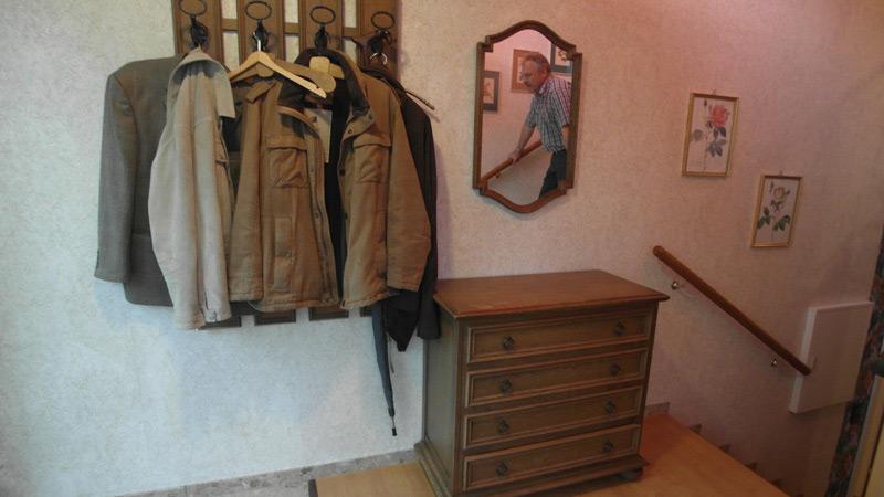 Eingangsbereich mit einer Kommode, neben der Garderobe und einem Spiegel