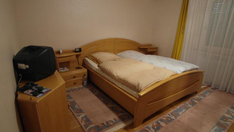 Weißes Schlafzimmer mit einem Parkettboden und mehreren bunten Teppichen