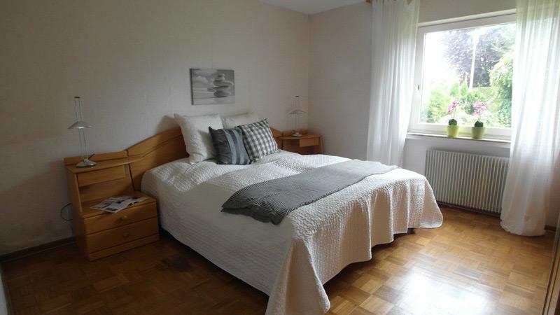 Weißes Schlafzimmer mit einem Parkettboden und einem Doppelbett
