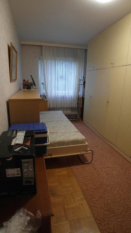Schlafzimmer mit Parkettboden und einem großen Wandschrank