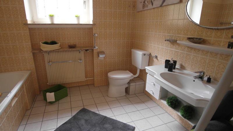 Beiges Badezimmer mit floralen Wandfliesen und einem weißen Boden