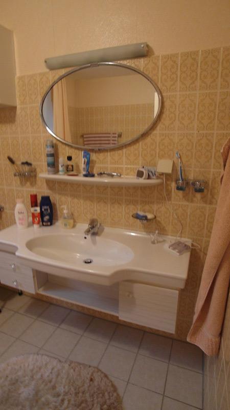 Weißer Möbelwaschtisch unter einem ovalen, beleuchteten Spiegel
