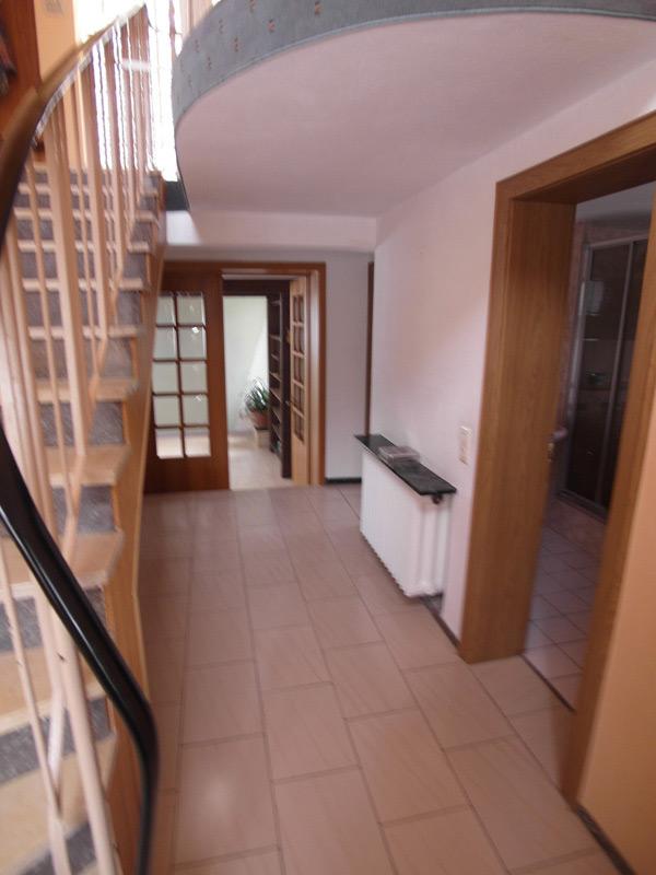 Treppenhaus mit einer Holz-Doppeltür und einem weiß gefliesten Boden