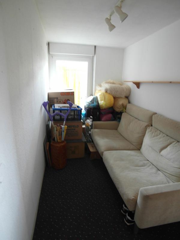Kleiner Abstellraum mit einem Sofa und dahinter Gerümpel