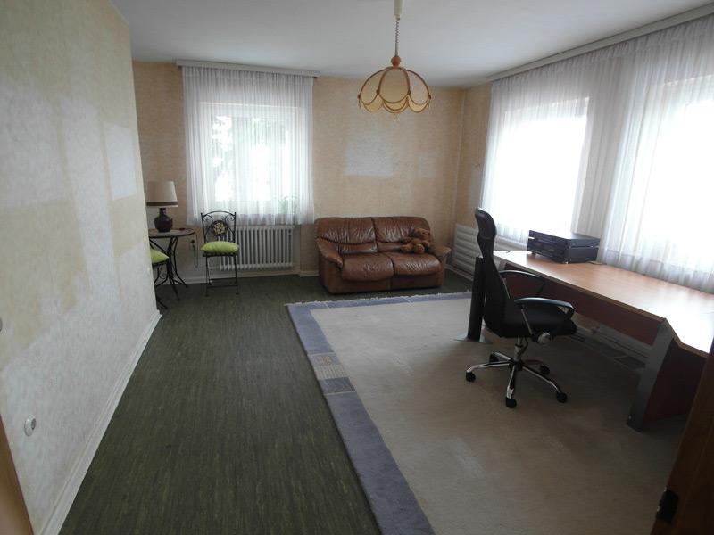 Beiges Arbeitszimmer mit dunklem Laminatboden, einer Couch und einem Arbeitstisch
