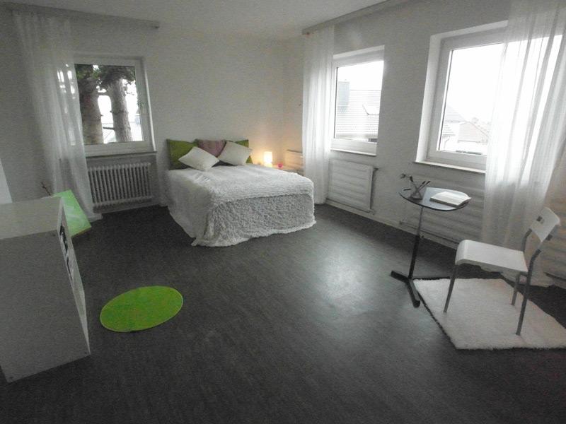Weißes Schlafzimmer mit einem dunklen Laminatboden, weißem Mobiliar und grünen Akzenten