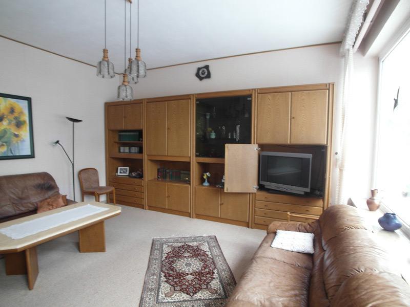Altmodisches Wohnzimmer mit großer Schrankwand und Leder Sofas