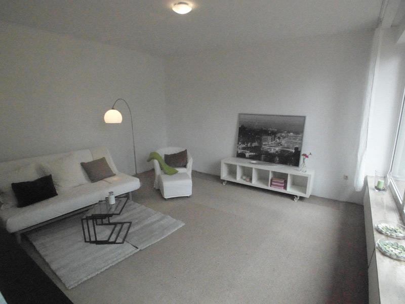 Weißes Wohnzimmer mit grauem Boden und weißem Mobiliar