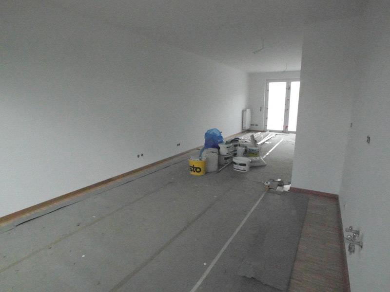 Weißes Zimmer im Aufbau mit abgedecktem Boden und Maler Utensilien