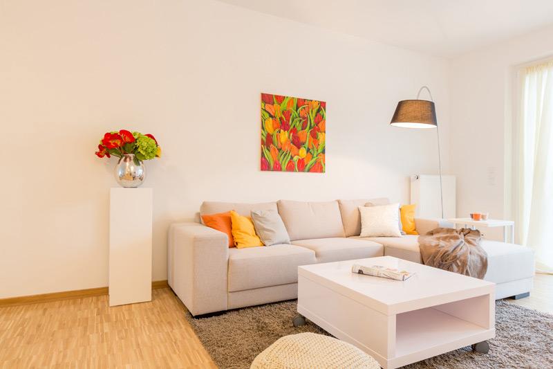 Weißes Wohnzimmer mit Laminatboden und farblichen Akzenten in Rot, Orange, Gelb und Grün