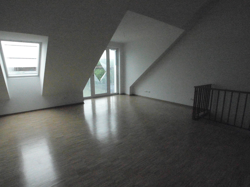 Leeres, weißes Zimmer mit einer hohen Dachschräge