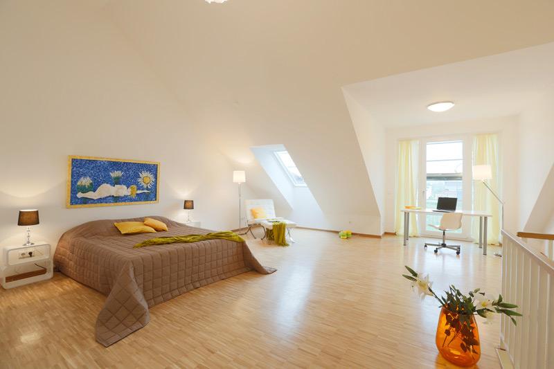Geräumiges, weißes Schlafzimmer mit einer Dachschräge und hoher Decke