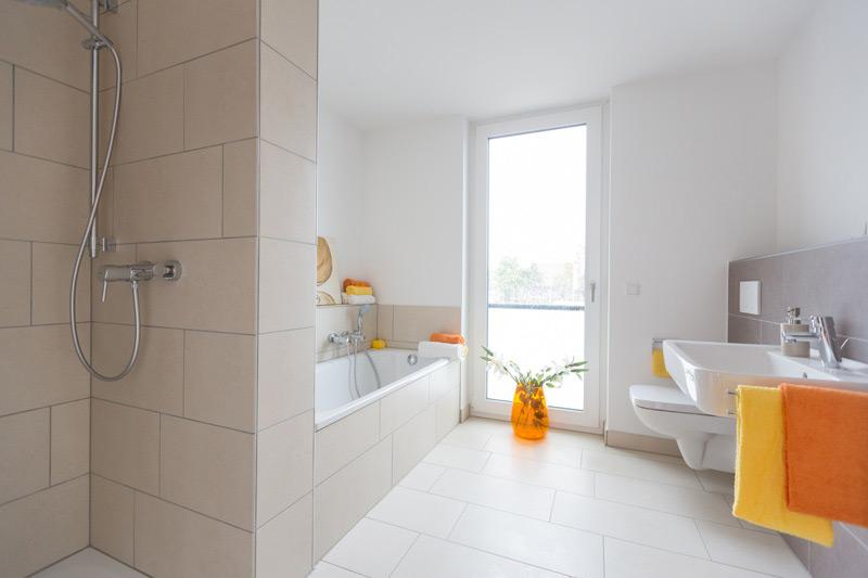 Helles, weißes Badezimmer mit Akzenten in Orange und Gelb