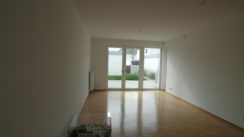 Weißes, leeres Zimmer mit Laminatboden