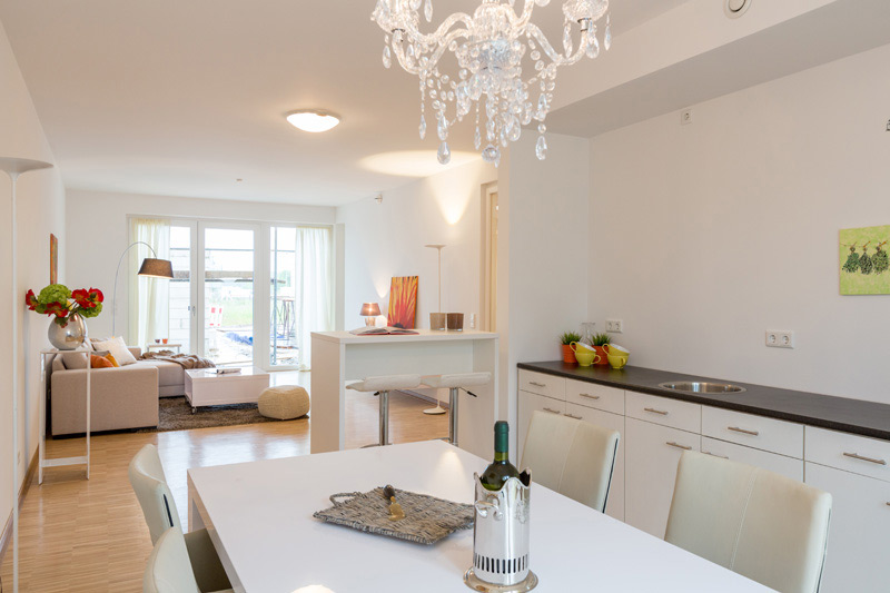 Weißes, helles Wohnzimmer mit einem Kristall-Kronleuchter