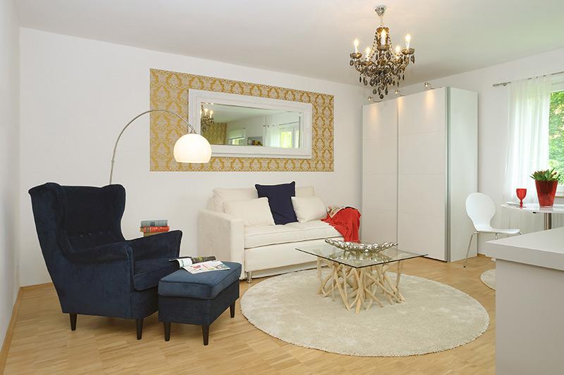 Weißes Wohnzimmer in edlem Stil mit einem Kronleuchter und einem floralen, gold-weißen Wandtattoo