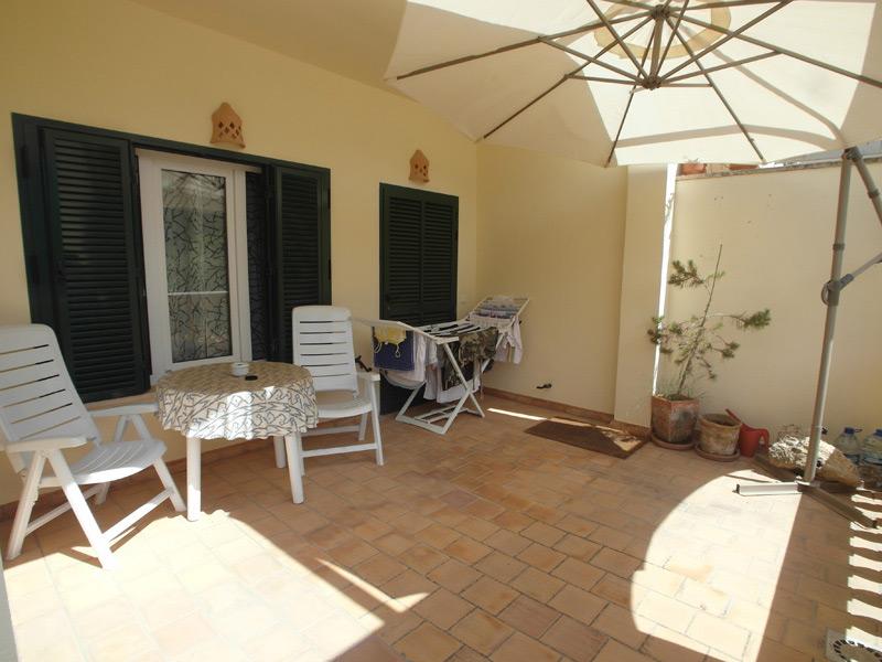 Balkon mit rot-braunen Bodenfliesen, Gartenmöbeln und einem Wäscheständer