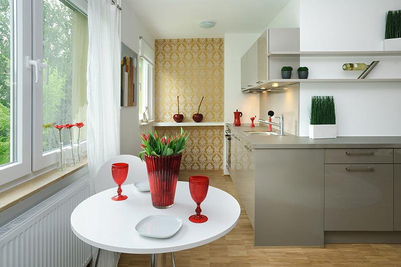 Weiße Küche mit einer grauen Küchenzeile und roten Akzenten durch Blumen und Geschirr