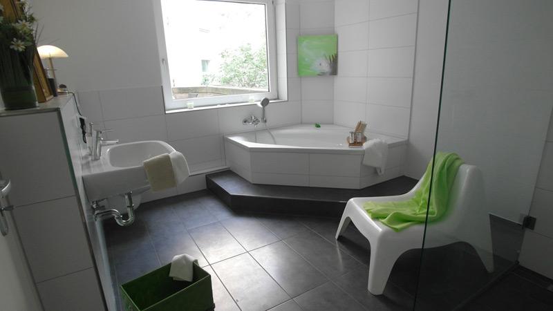 Weißes Badezimmer mit dunkelgrauem Boden und einer Eckbadewanne mit Stufe