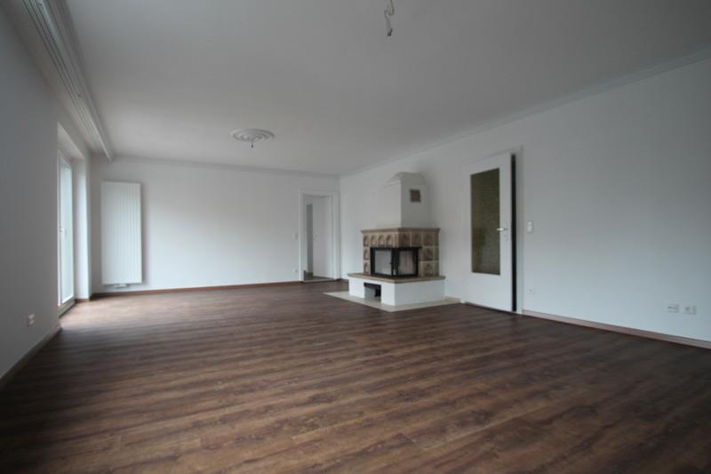 Weißes Wohnzimmer mit Laminatboden und einem kleinen Kachelofen