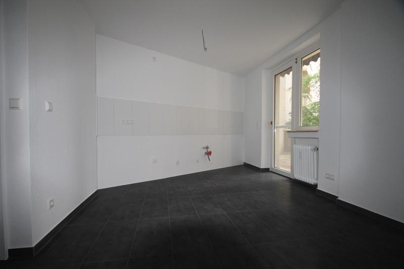Leerer, weißer Raum mit schwarzen Bodenfliesen und einer Fenstertür